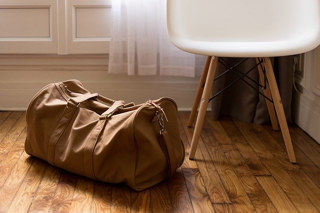 A packed duffle bag says ready to go and an inviting chair says ready to stay