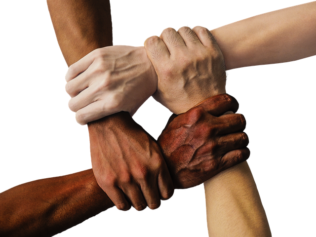 Diversified hands clasped on each other's wrists together in unity