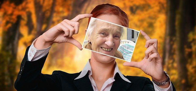 Photo of a smiling older woman' face held up in front of a smiling younger woman's face - embracing youthful attitude even as we age